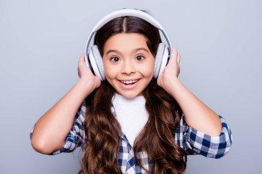 Close up portrait of happy joyful, cute, shocked kid holding ear