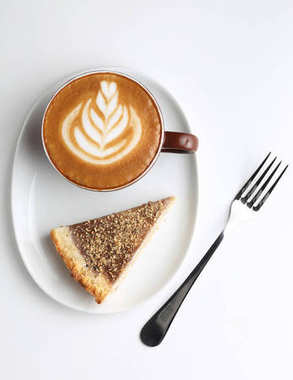 Cup of cappuccino and a piece of cake. Latte art. Isolated on white background