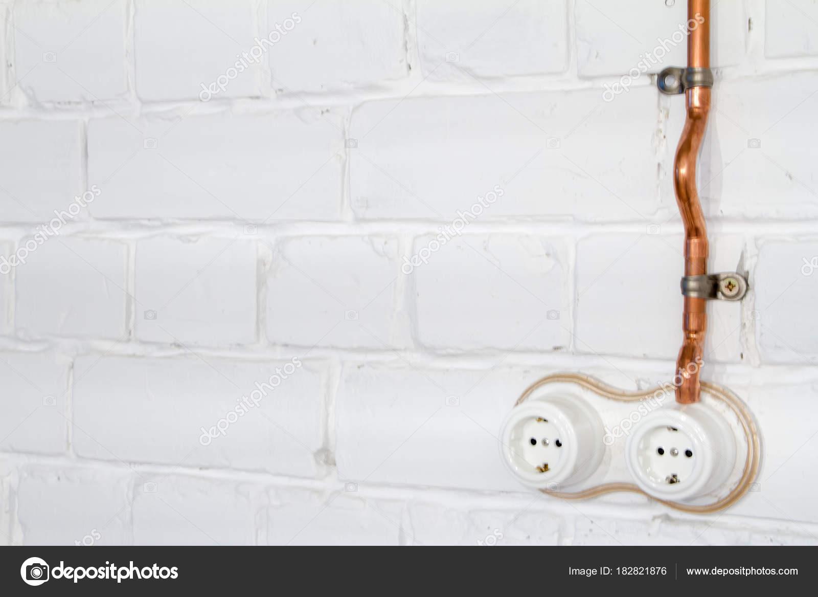 Ein Vintage Outlet und elektrische Verdrahtung in einem Kupferrohr ...