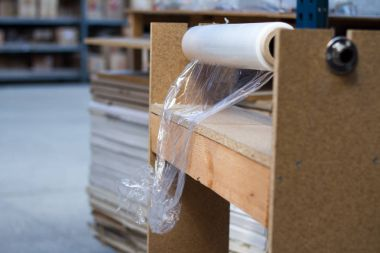 A roll of polyethylene film for packaging.Lies on the desktop and a little expanded.