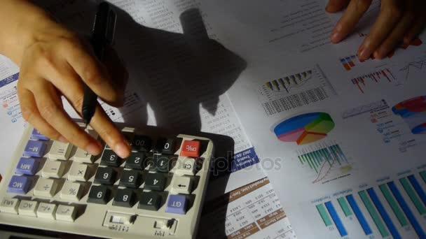 calculator.examining üzleti grafikonon pénzügyi adatok ellenőrzése.