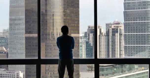4k, egy üzletember, kilátással a városi irodaház ablakából.