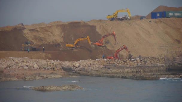 Chian-Aug 22,2017:Excavator working  dumper truck on construction site near sea.