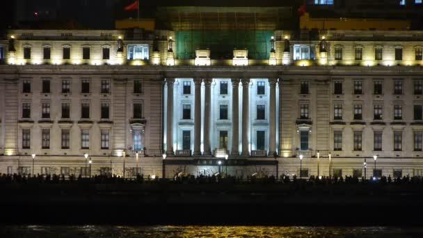 mozgó emberek sziluettje régi európai stílusú épület háttér éjjel.