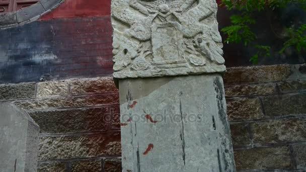 Kő emlékmű-a templom bejáratánál, remegés tree árnyékok, sárkány mintával