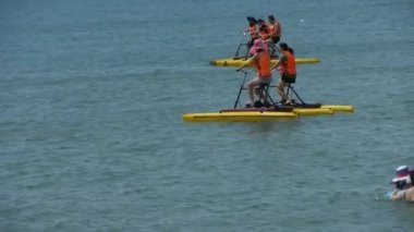 China-Aug 08,2016:People play water bike toys on sea.