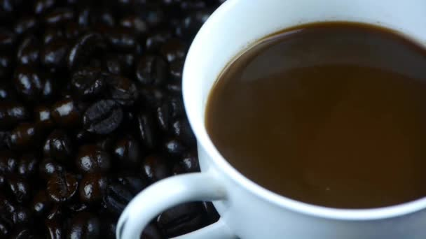 pouring milk into a cup of coffee  coffee beans background,top view.