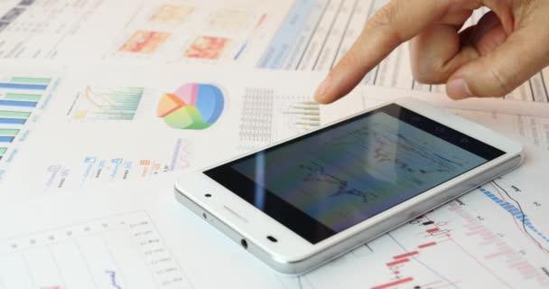 4k Businessman browsing financial news on smartPhone,finance pie charts on tabl
