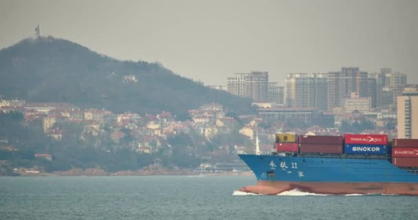 China-Apr 08,2017:4k Cargo Container Ships Through The QingDao Harbo,moder urban building,china.