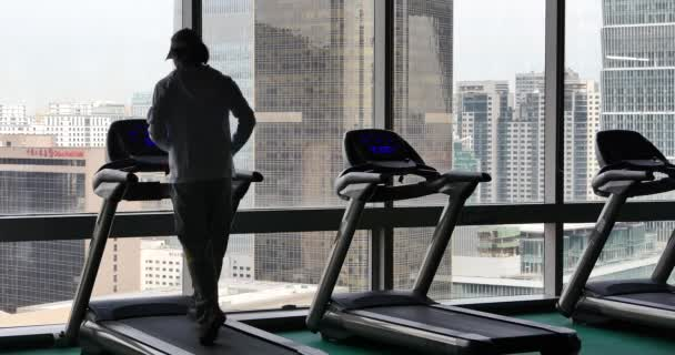4k,male running on cardio treadmills,urban business building,overpass traffic from window.
