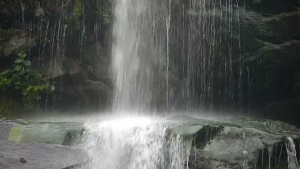 vodopád na útesech v horách, tekoucí do rybníka jezero
