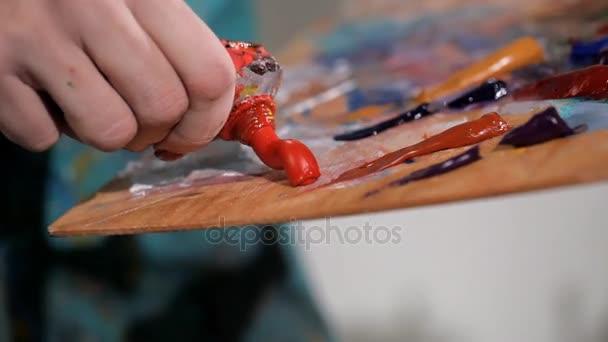 Junge Künstlerin drückt orangefarbene Farbe auf die Palette