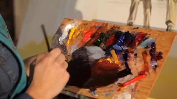 Junger Künstler mischt helle Farbe auf die Palette