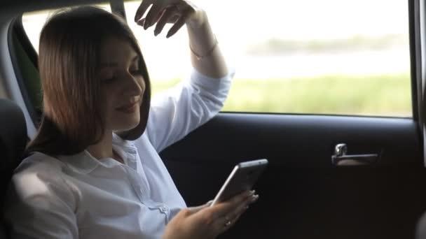 wunderbare Businessmädchen fährt im Taxi und benutzt das Telefon