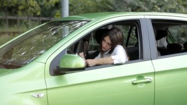 Girl in a car talking on the phone about a business and making notes in a notebook