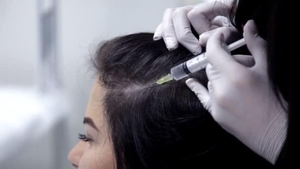 Doktor kosmetička provede postup mezoterapie, injekce do kůže hlavy. Detail