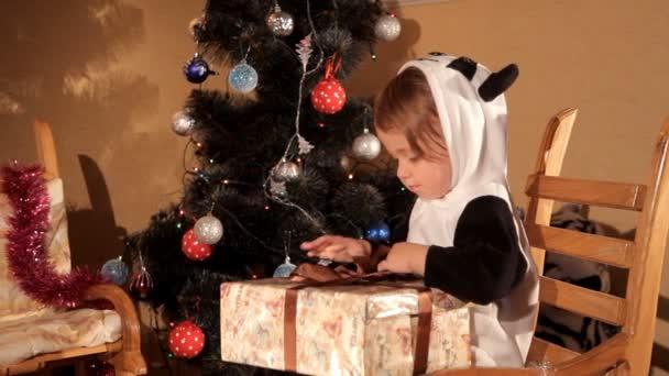 Kind öffnet ein Neujahrsgeschenk in der Nähe eines Weihnachtsbaums