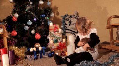 Little girl is playing near a Christmas tree with a New Years gift