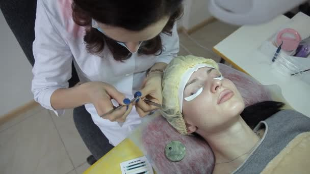 Roztomilá dívka kosmetička zvyšuje řasy. Prodlužování řas v kosmetickém salonu