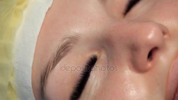 Krásná dívka otevírá její modré oči po prodlužování řas