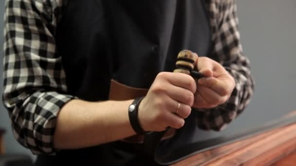 The master processes the edges on the leather strap with a special tool