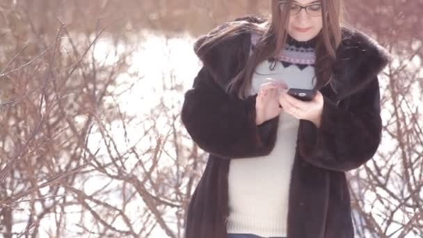 Young girl in a snow-covered landing uses a mobile phone, correcting her hair