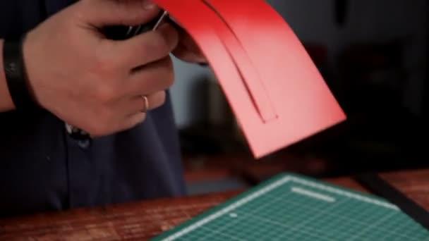 Průmyslové nože muž vyjme obrobek z kůže