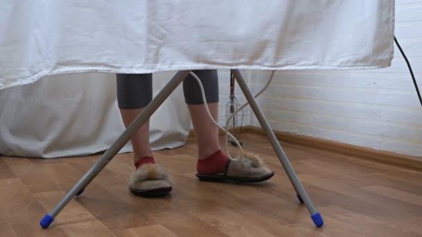 Frauenbeine sind hinter dem Bügelbrett und bügeln Dinge.