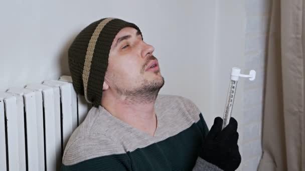 Mann überprüft Temperatur der Heizbatterie. Kalte Winter, Kälte im Haus, Wohnung. Mann wärmt sich in der Nähe einer Heizbatterie