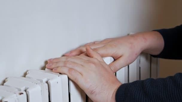 Ein Mann mit Hut wärmt seine Hände an einem Heizkörper in Wandnähe. Kälte in der Wohnung, schlechte Heizungsanlage