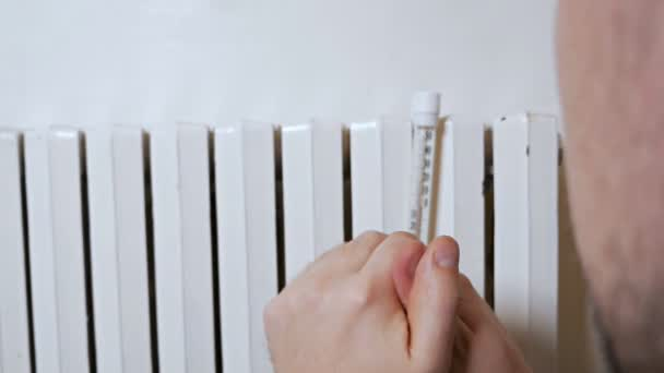 Ein Mann misst an einem Wintertag in der Nähe einer Batterie die Lufttemperatur in einem Haus. schwache, schlechte Heizung. in warmer Kleidung im Haus, Wohnung