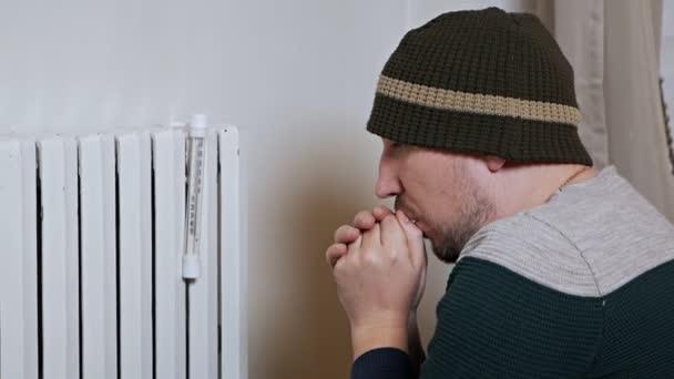 Muž měří teplotu vzduchu v domě v zimním dni poblíž baterie. Slabé, špatné topení. V teplém oblečení v domě, byt