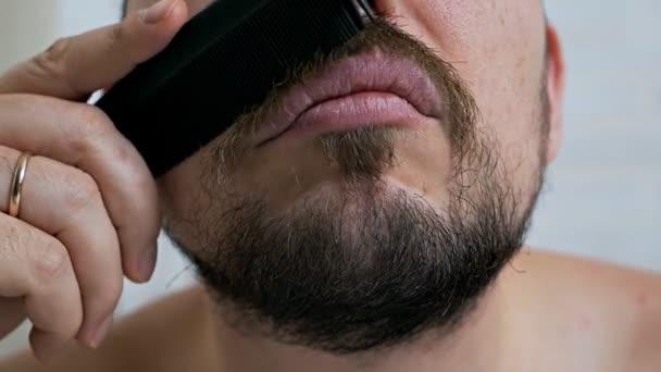 Vousy muži zblízka. Hipster muž česání vousy před zrcadlem
