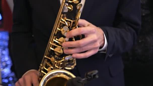 Egy szmokingszaxofonos szaxofonon zenél. Egy zenész szaxofonozik egy koncerten. Jazz est. Élő műsor