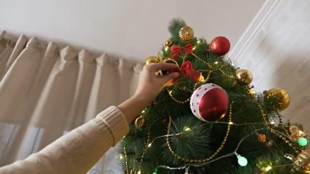 Ženské ruce zdobí vánoční stromek s krásnými skleněnými kuličkami