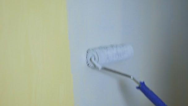Bauwalze streicht die gelbe Wand mit grauer Farbe an