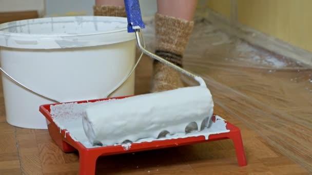Mädchen schwingt eine Bauwalze mit weißer Farbe in eine Pfanne. Selbstreparatur im Zimmer