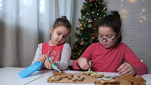 Kids bake christmas cookies at home.The process of decorating Christmas cookies. Children decorate the gingerbread cookies in the form of a Christmas tree and little men