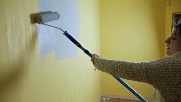 Ein fröhliches Autodidaktin mit einer Bauwalze bemalt eine gelbe Wand mit grauer Farbe. Unabhängige Wohnungsreparatur. Frische Reparaturen nach dem Umzug in eine neue Wohnung