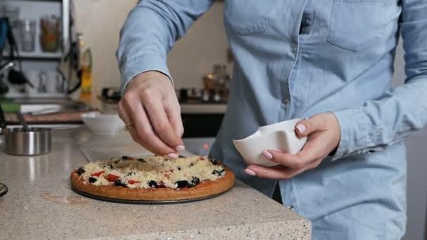 Ruce mladé dívky sypou pizzu strouhaným sýrem. Manželka připravuje pizzu pro svého milovaného manžela