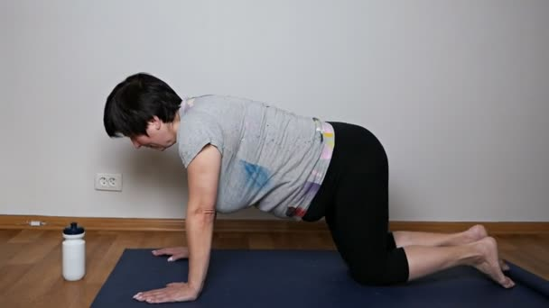 Healthy senior woman doing pilates or yoga, stretching exercises