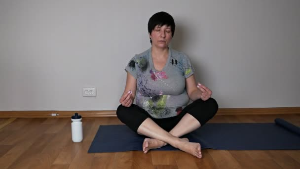 Active positive elderly woman practices yoga, breathing technique sitting on the living room floor