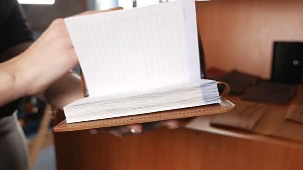 Bőrnapló, jegyzetfüzet bemutató egy nő kezében. Bőrműhely