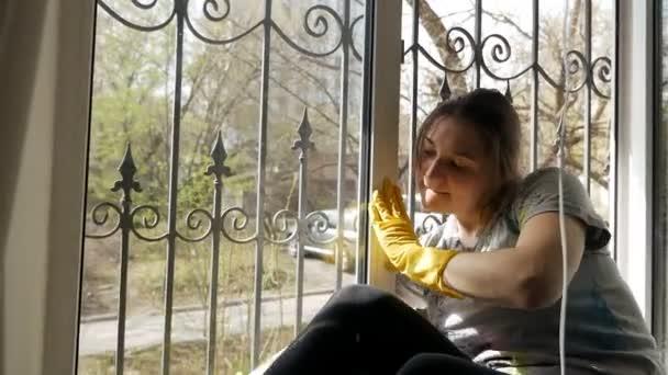 Házi rutin. Egy nő sárga kesztyűben ablakot mos.