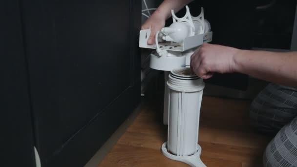Instalatér nebo Man ručně vyměnit zásobní vložky pro vodní filtr v kuchyni. Pevné čištění vodovodního systému. Muž nastaví vodní filtr.