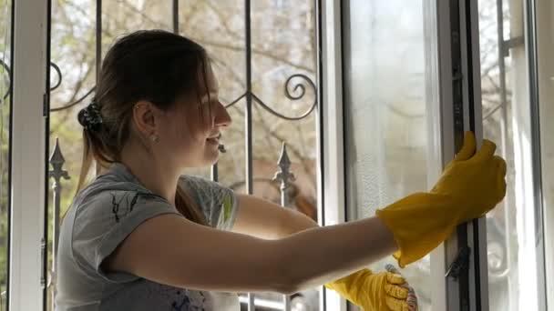 Domácí rutina. Žena ve žlutých rukavicích myje okno