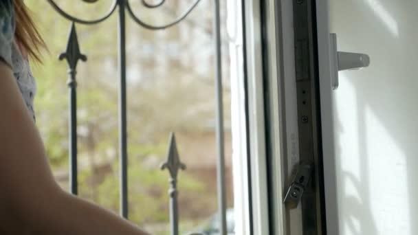 Menschen, Hausarbeit und Haushaltskonzepte - Frau in Handschuhen wäscht zu Hause Fenster mit einem Lappen