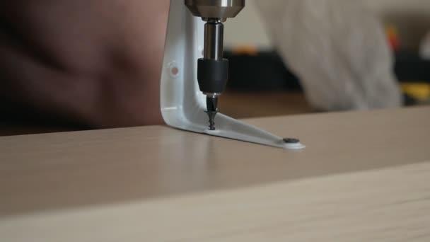 Muž dělník utáhne šroub šroubovákem. Kroucení šroubováků v dřevěné desce. Truhlářské a životní styl stavební práce close-up
