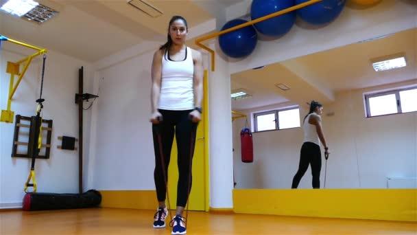 Mladá žena silné tmavé vlasy dělat cvičení v tělocvičně
