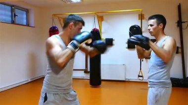 Two strong young boxers doing boxing exercises in the gym.